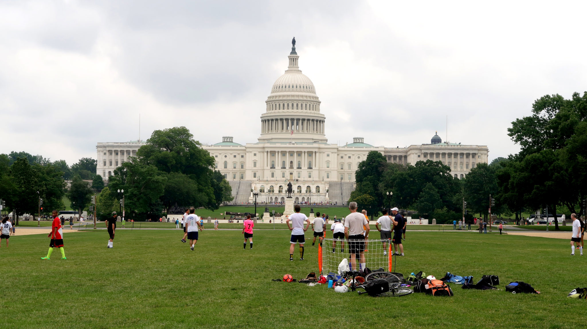 Des personnes jouent au football dans le National Mall devant le Capitole, Washington DC.